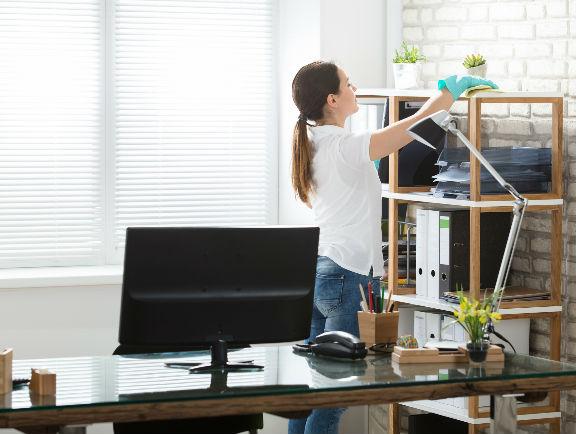 Mujer aseando el estante de acero de su oficina